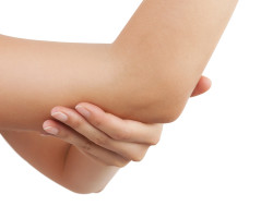 Elbow pain. Beautiful female holding her elbow. Pain concept.